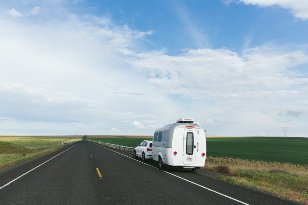 airstream nest being towed by audi on open highway with blue skies