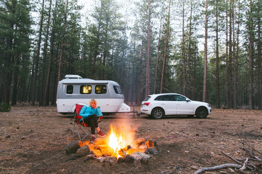 airstream nest at campsite with campfire and audi with laura austin in woods