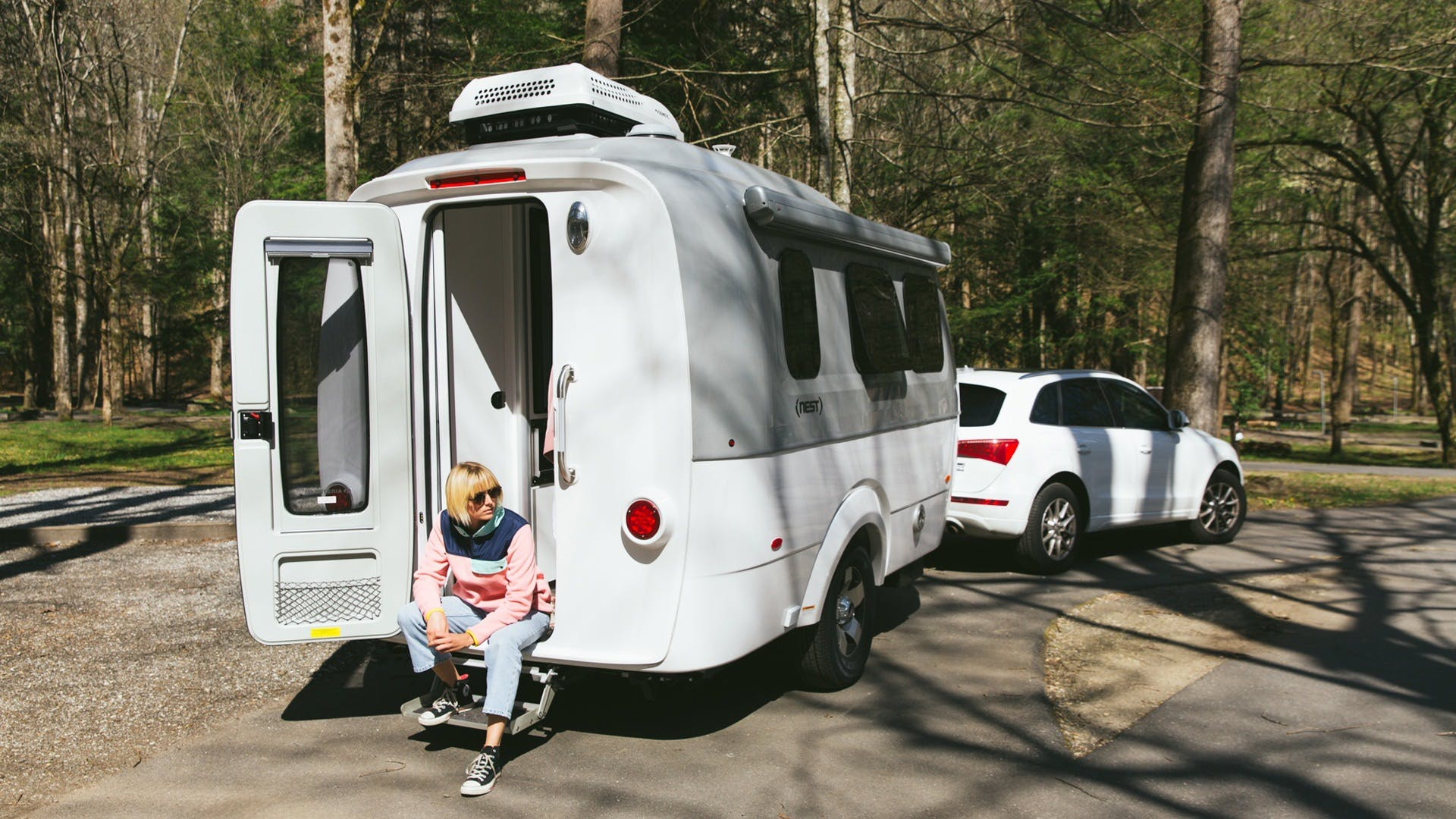 Airstream Travel Trailer Nest rear door open trees camping campground road