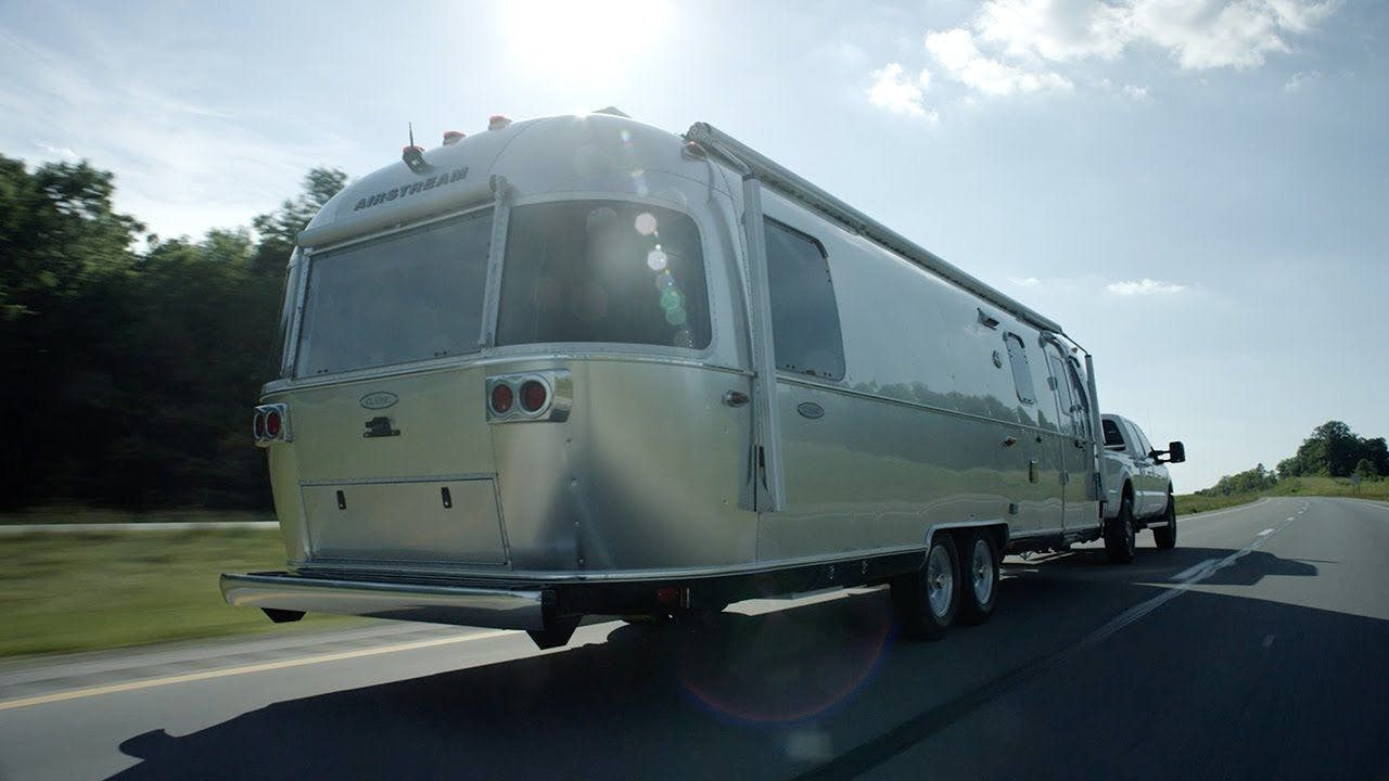 Airstream Travel Trailer aluminum Classic towing road trees sun sky