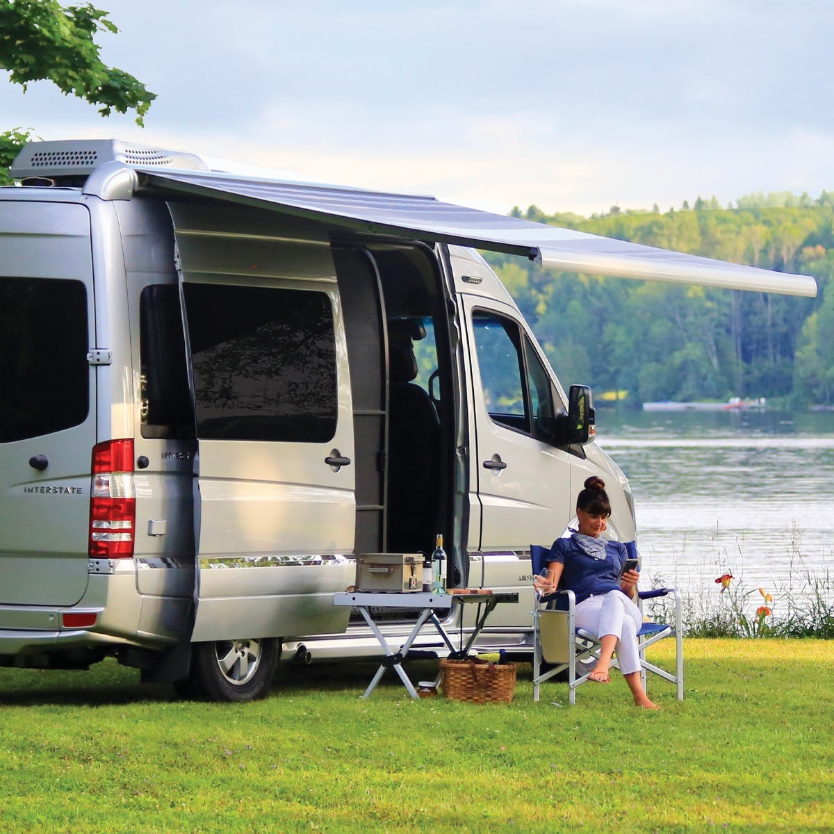 Airstream Interstate Nineteen Mercedes Benz grass water trees explore travel woman