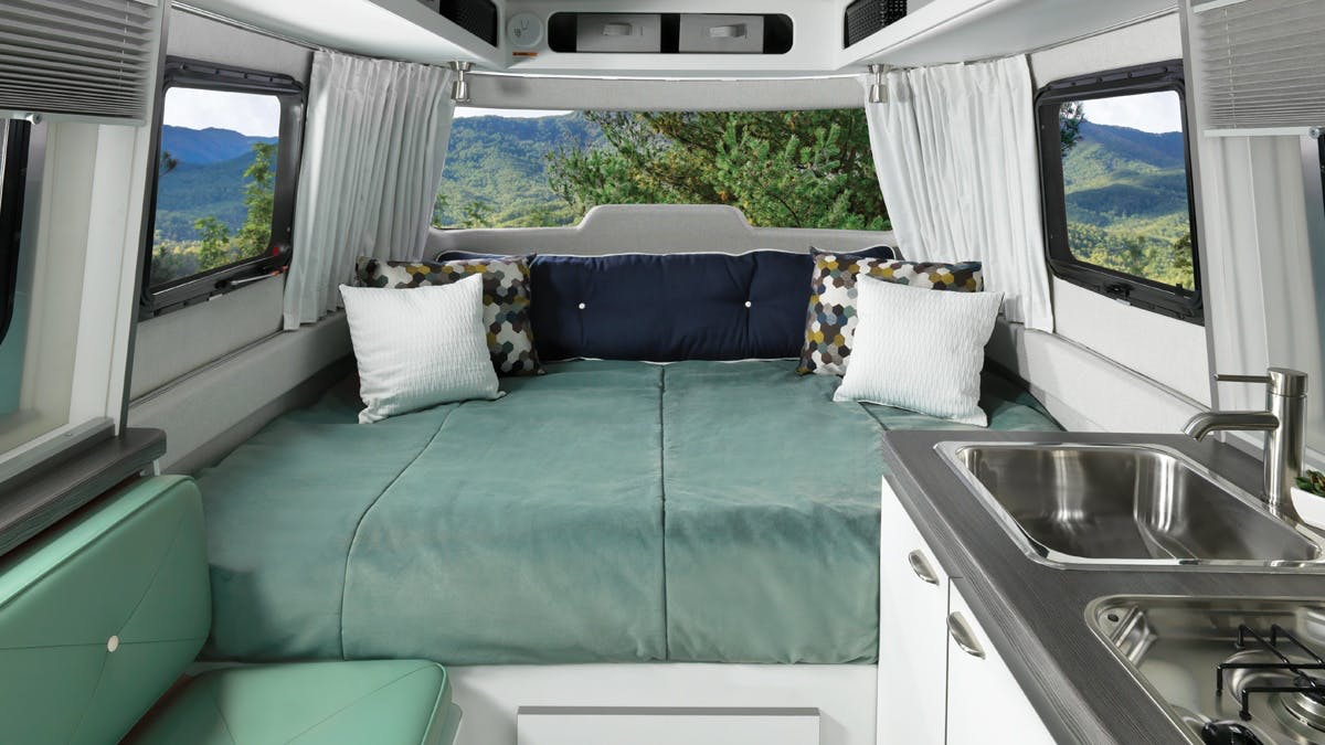 Nest by Airstream interior clutch blue bed fixed pillows sink windows curtains seat