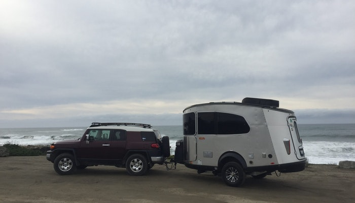 Airstream Travel Trailer RV Camper Trailer Basecamp being towed by Toyota