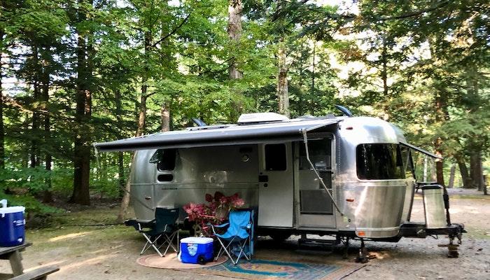 Airstream Travel Trailer RV Camper Trailer set up at campsite in woods