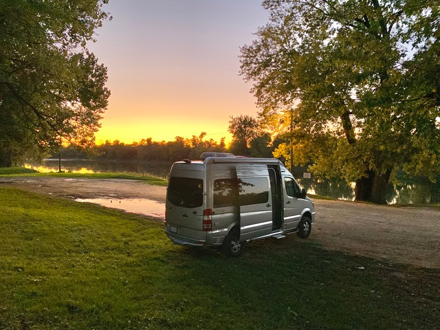 Airstream Interstate Nineteen Sunset by water and trees