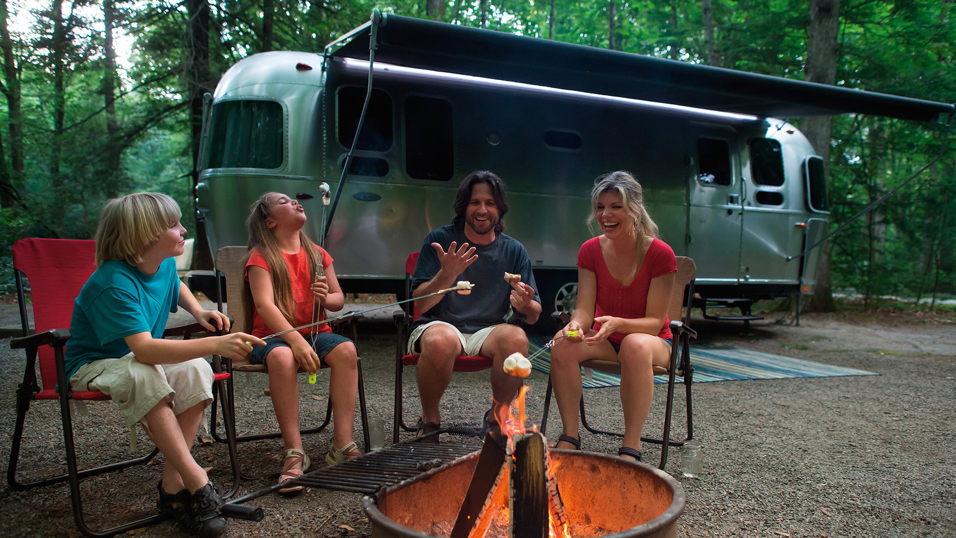 Family-Traveling-Together-by-Fire-Pit-Airstream-Flying-Cloud