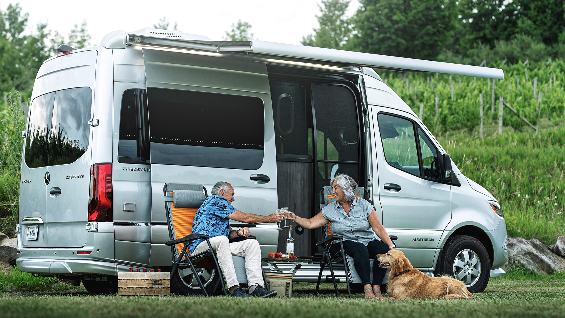 A couple sitting outside touring coach with dog