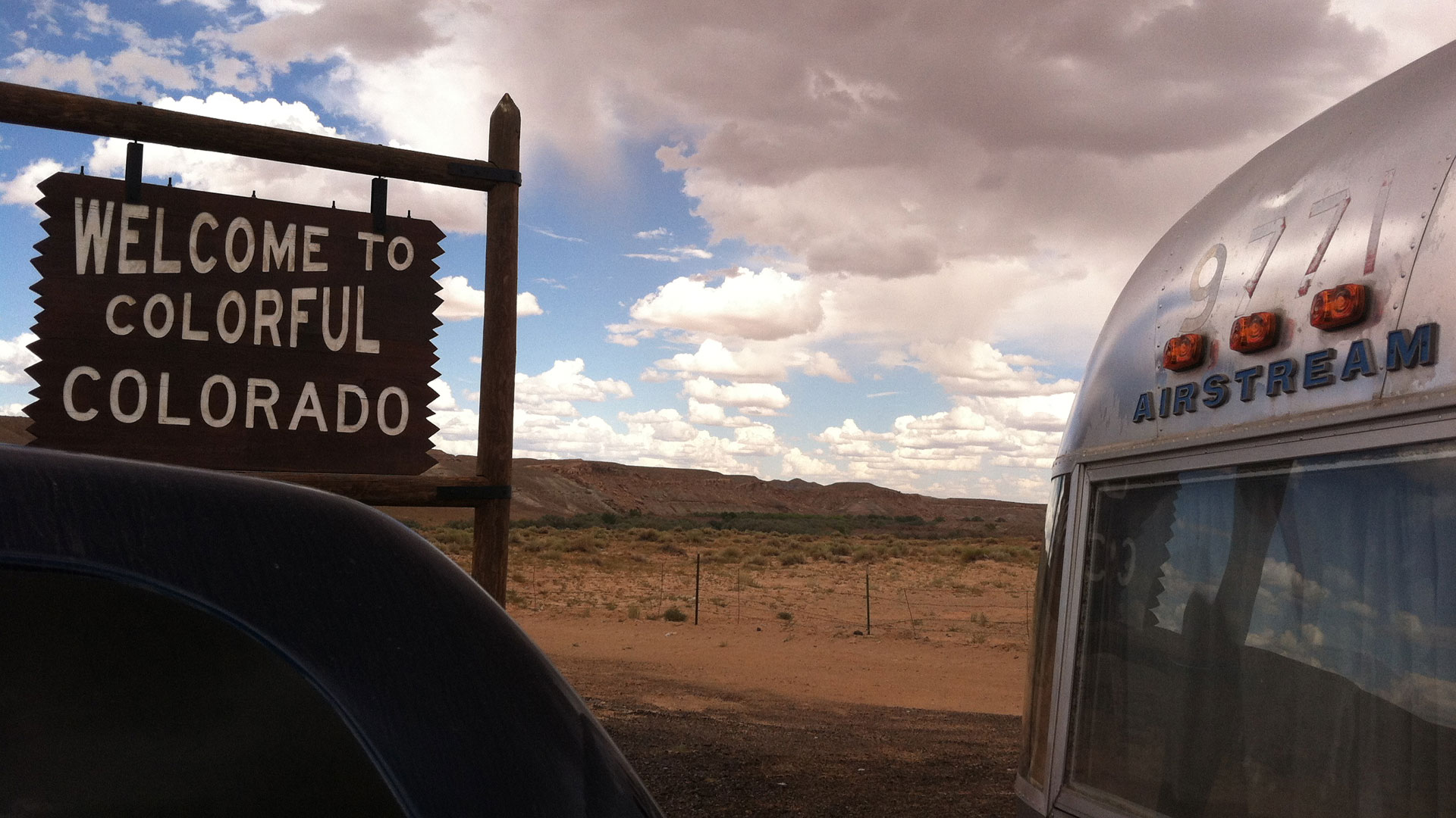Airstream Classic Trailer sitting in front of a Welcome to Colorado sign