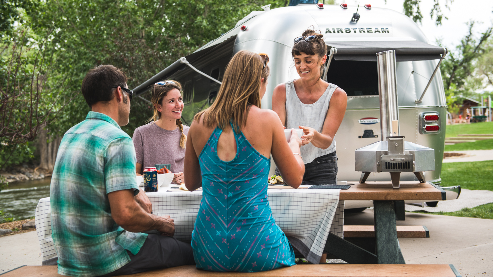 people-hanging-out-at-a-picnic-table-by-their-Airstream
