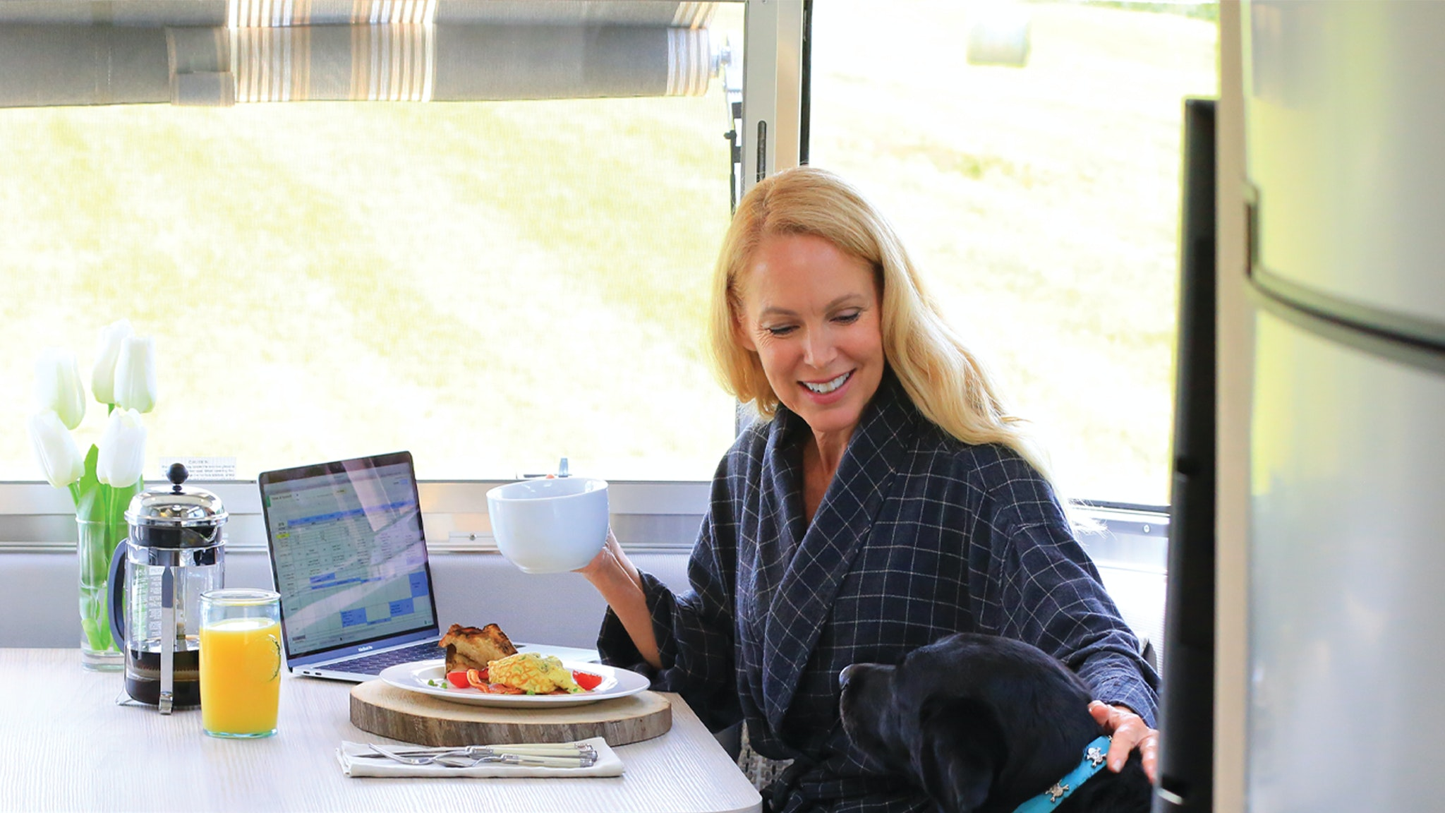 Female Airstreamer sitting in the Galley of her trailer with her dog
