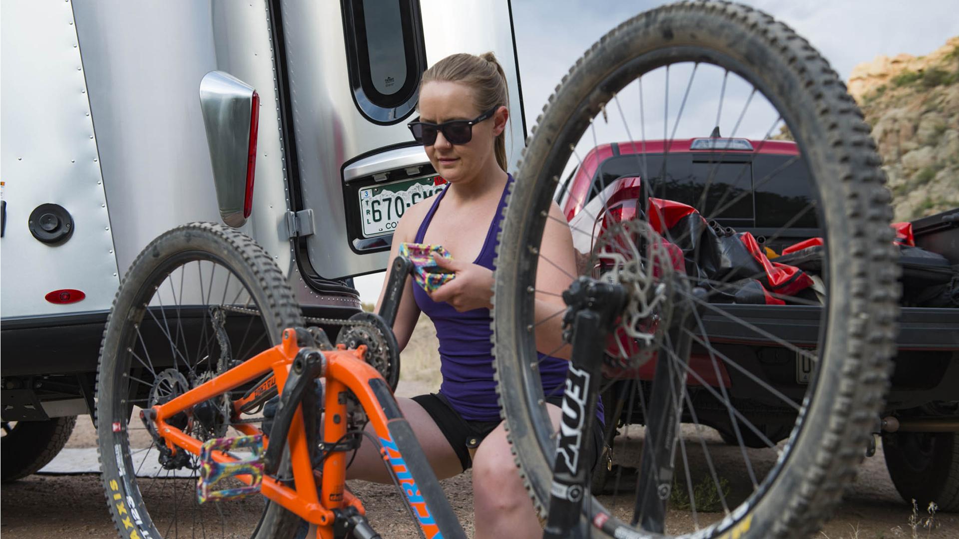 A female airstreamer fixing her bike