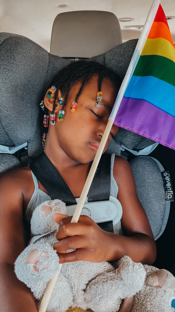 Charlotte sleeping in her car seat with a LGBTQ+ flag