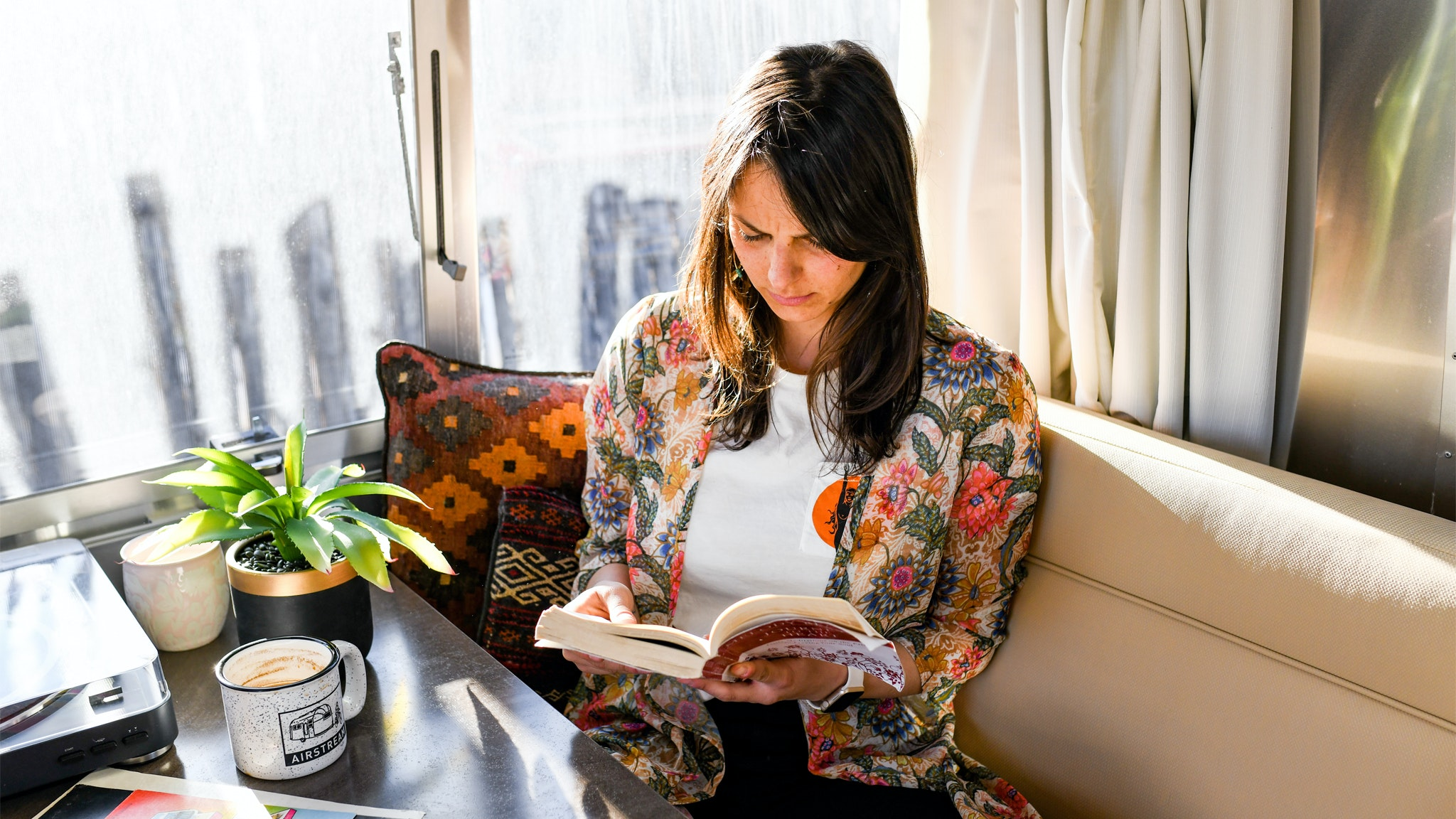 Danielle sitting in the galley of an Airstream Travel Trailer reading a book