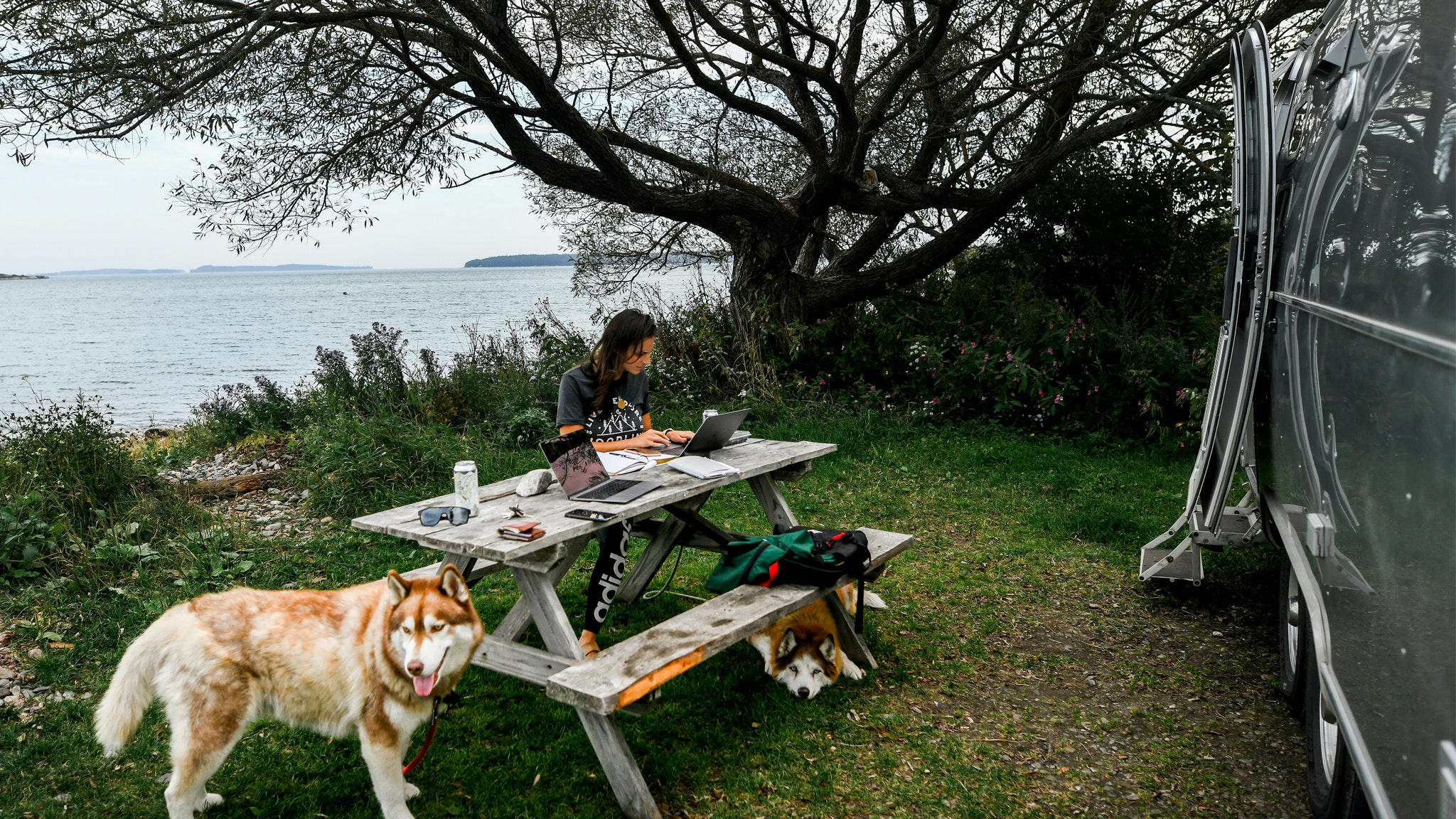 Danielle working at a picnic table outside of her Airstream Travel Trailer