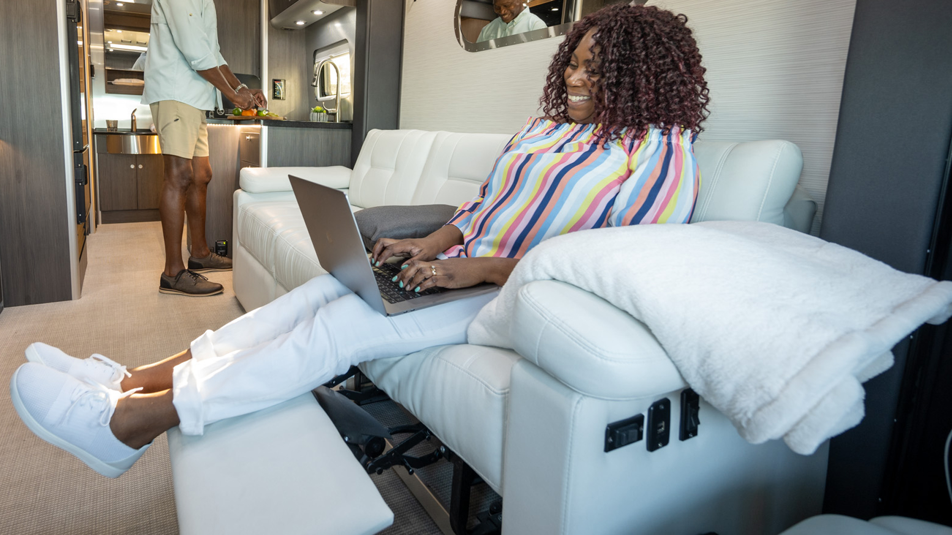 Female Airstreamer sitting on the sofa in her Touring Coach on her computer