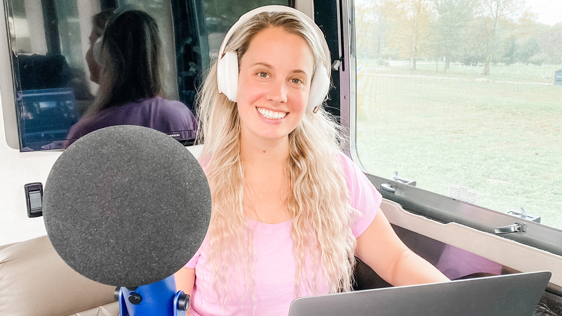 Lauren sitting in the galley of her Airstream Travel Trailer creating a podcast