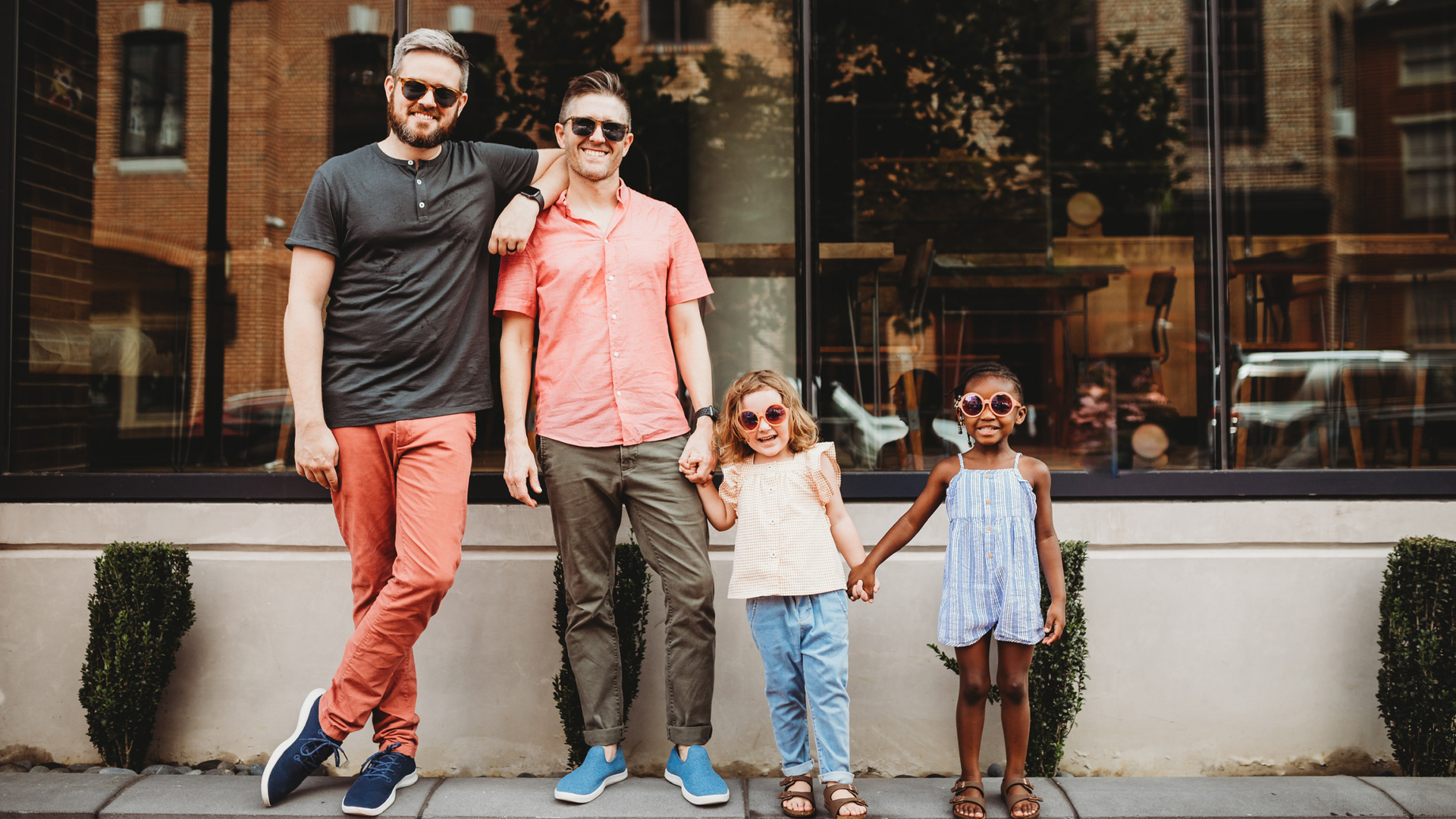 Jonathan and Thomas with their daughters outside with sunglasses on
