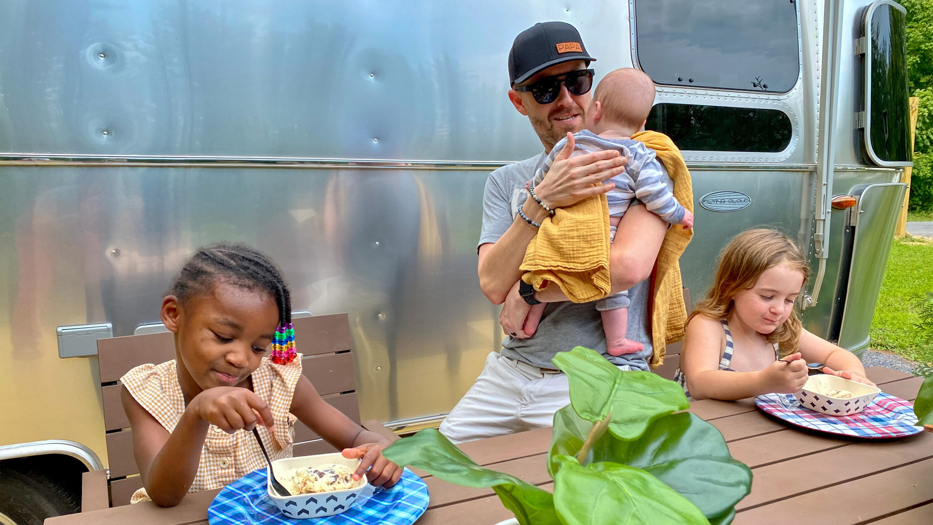 Jonathan and Thomas's Kids sitting at a table outside by their Airstream Travel Trailer