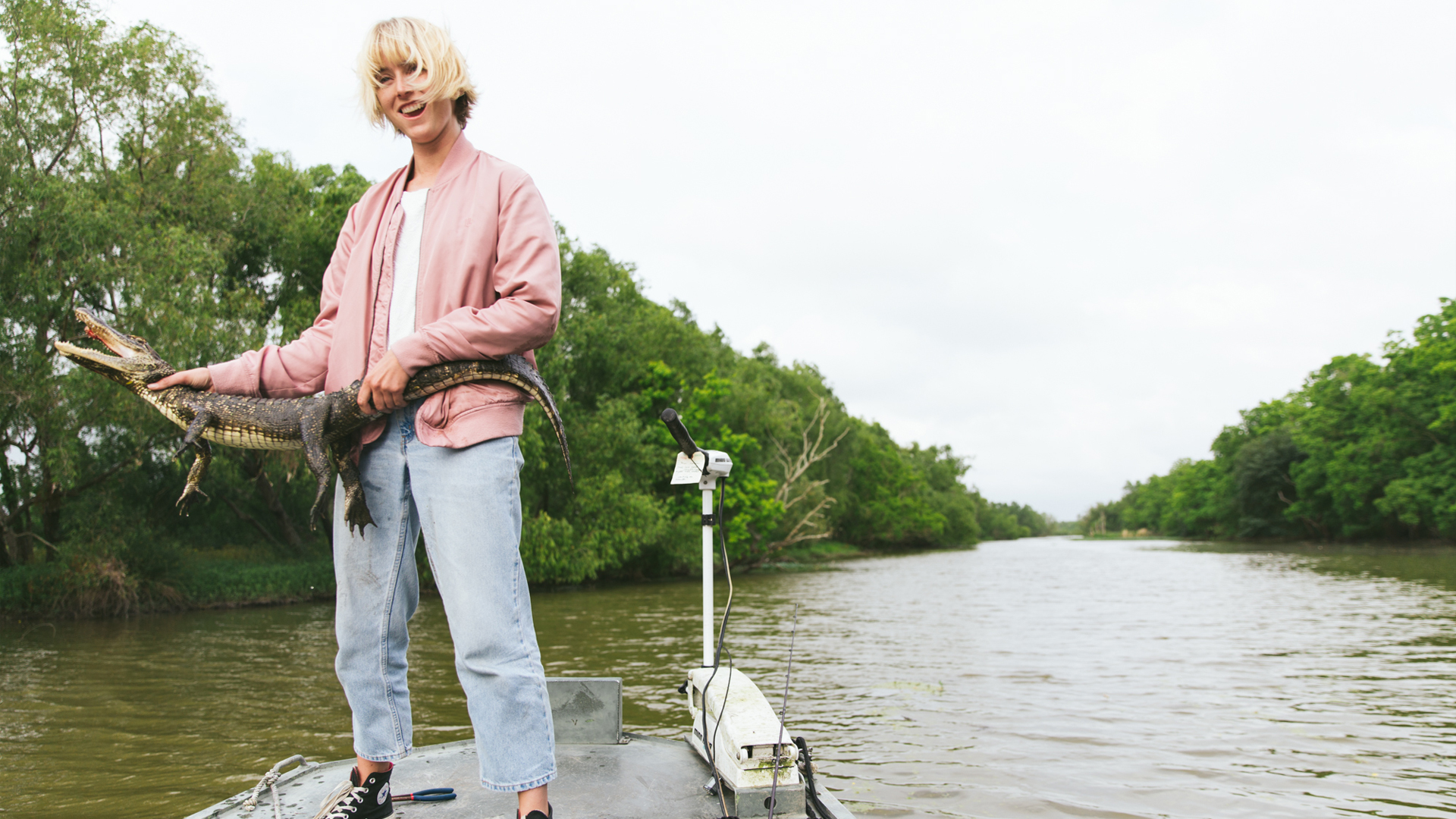 Laura Austin holding an alligator on a boat