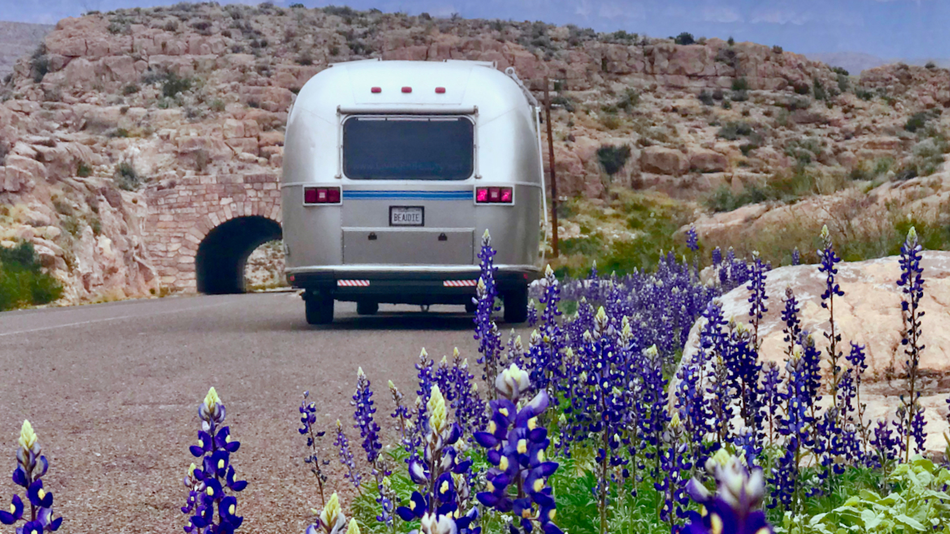 Airstream driving down the road in the desert