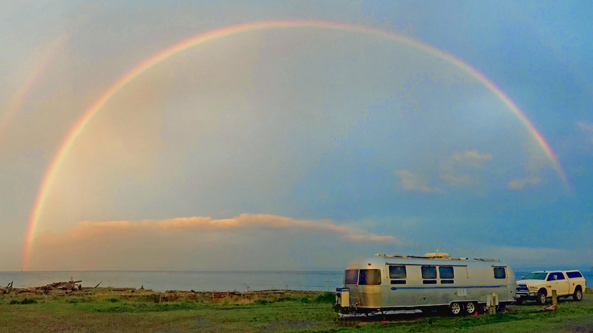 Airstream parked with a rainbow in the sky