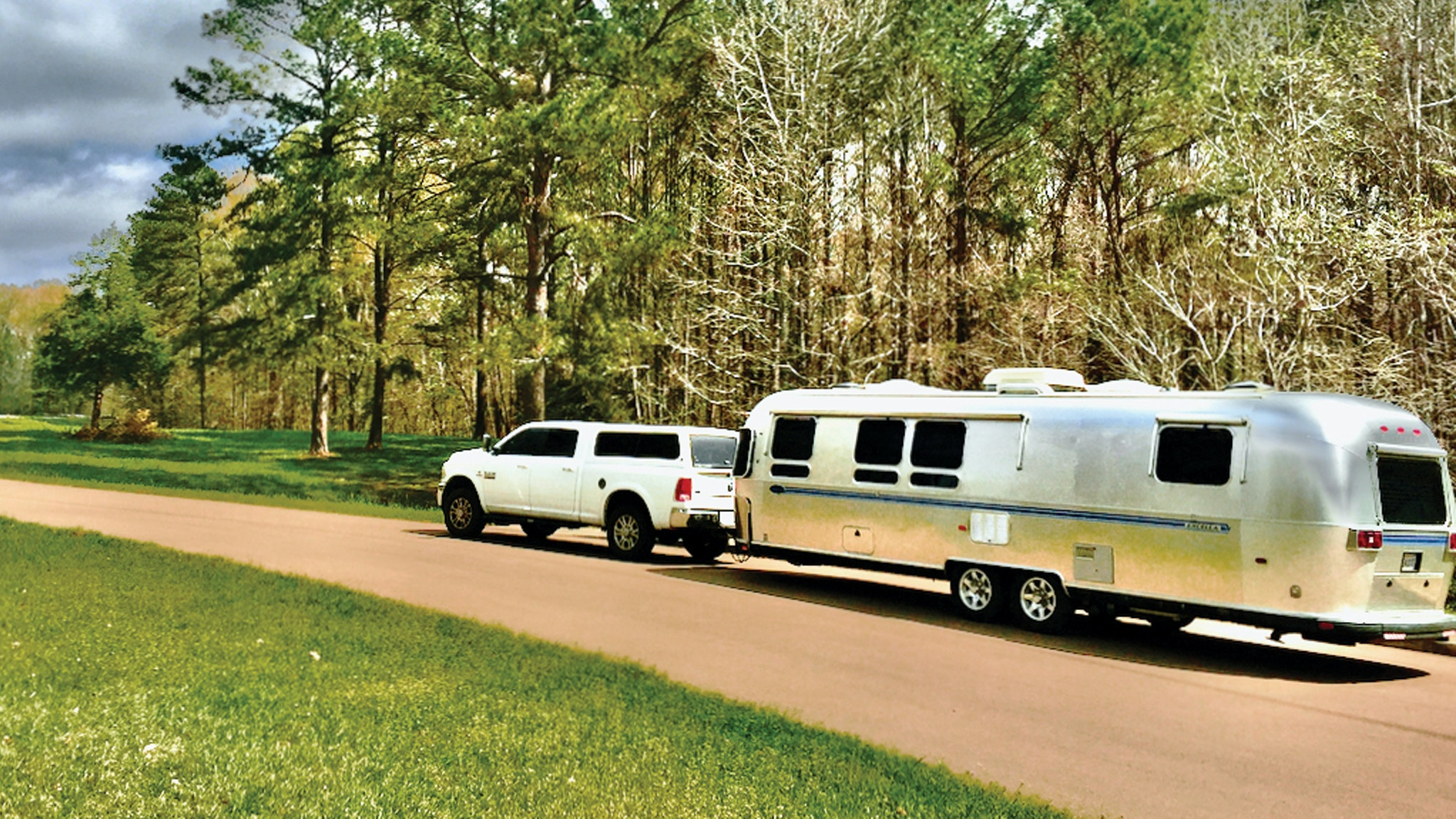 Airstream named Beauty driving down a lane