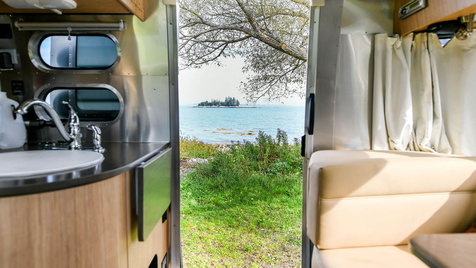 Looking out of an Airstream at a lake in Maine