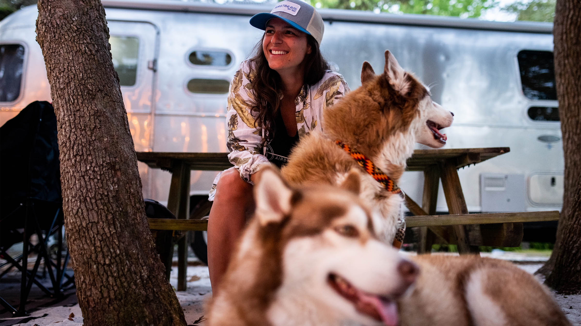 A woman and her two dogs sitting at a campground outside of her Airstream Travel Trailer