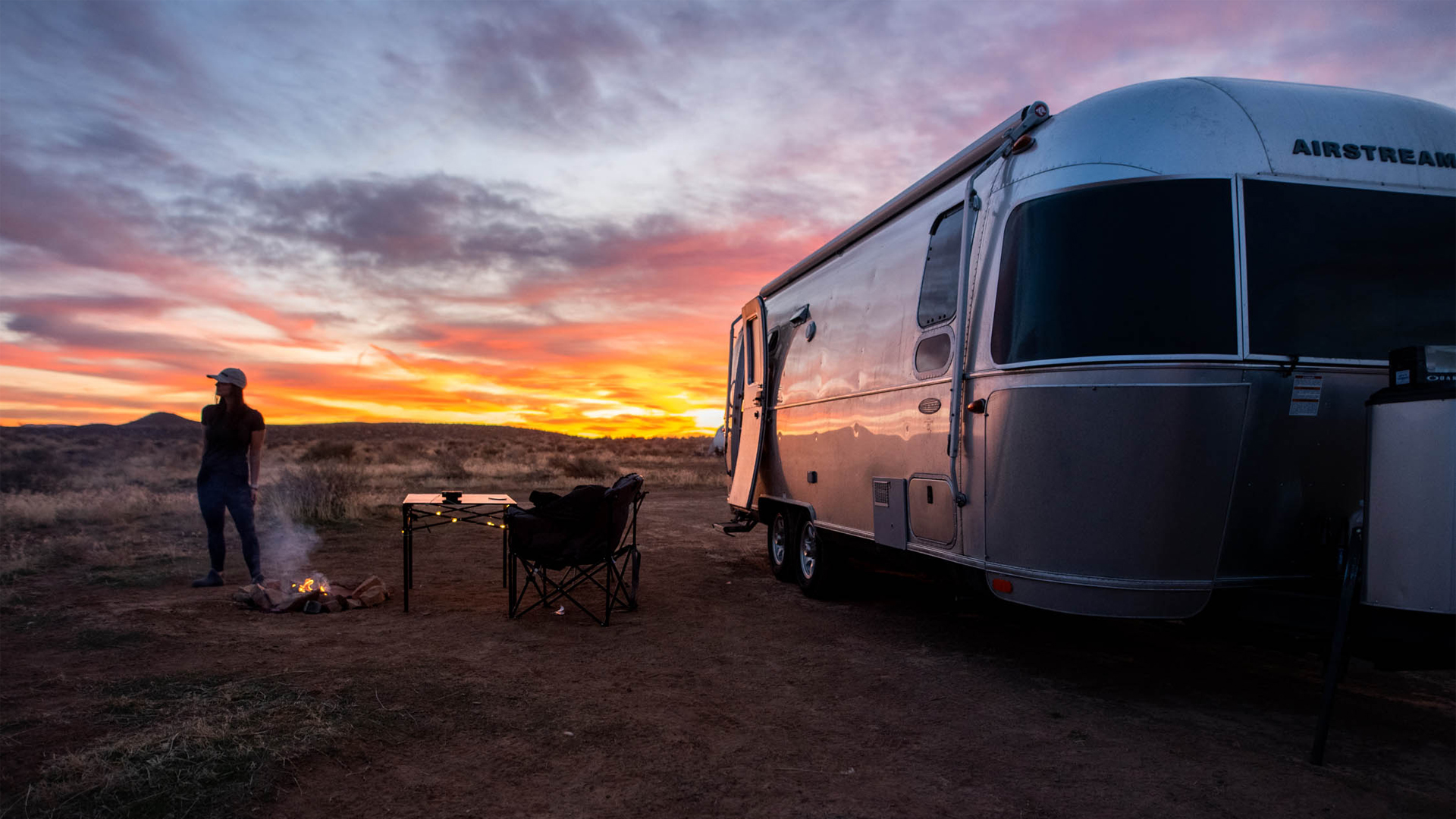 Woman watching the sun set outside of her Airstream Travel Trailer