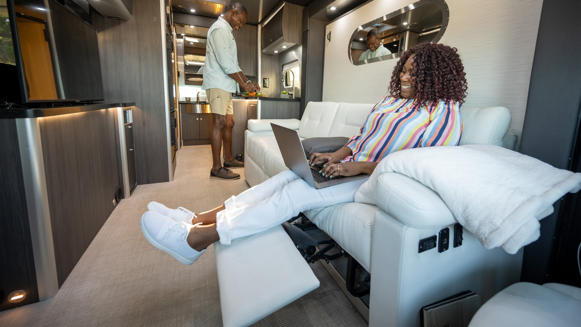 A couple sitting in an Airstream Class B Motorhome