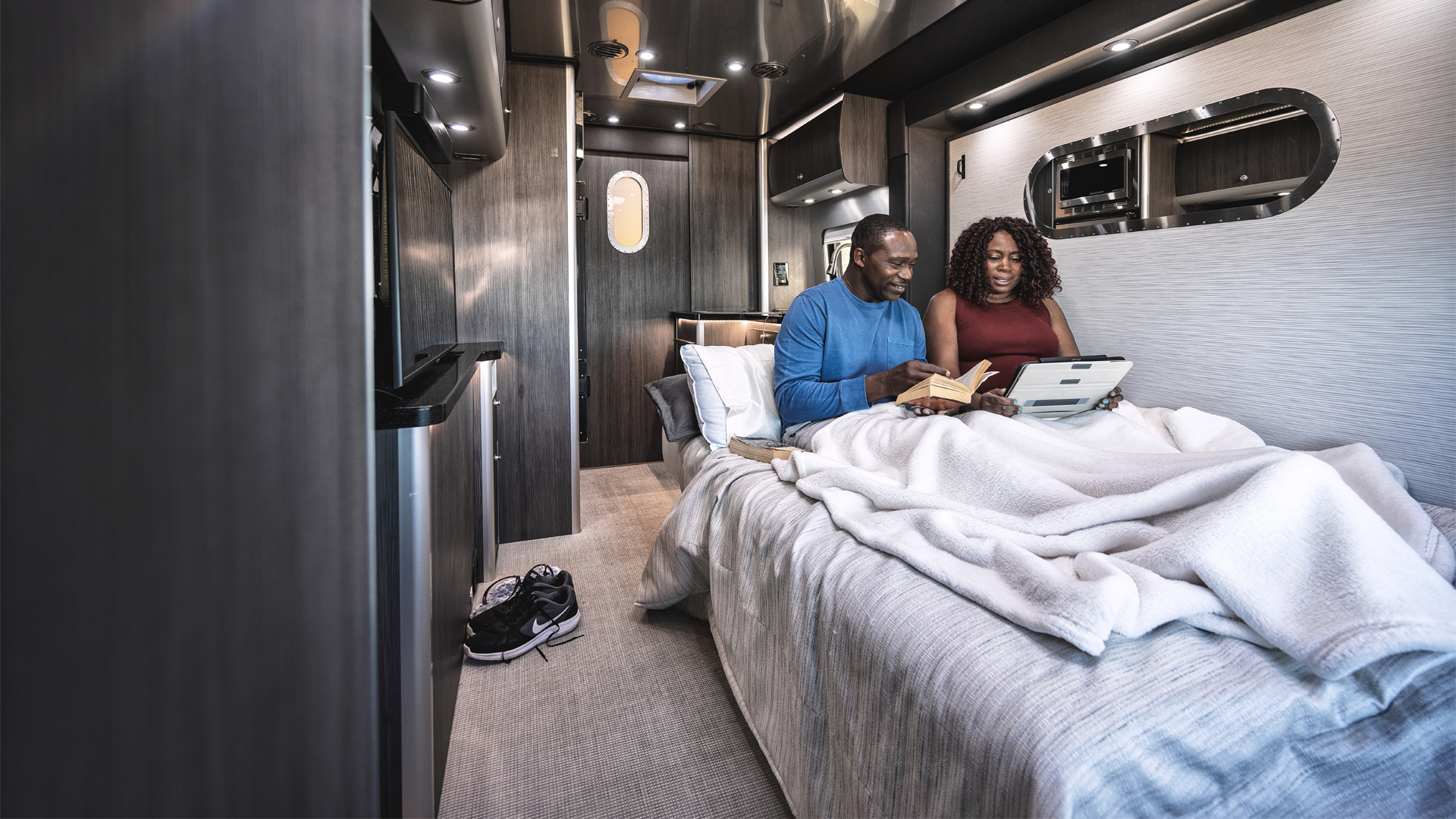 A couple sitting on the bed reading in their Airstream class B motorhome